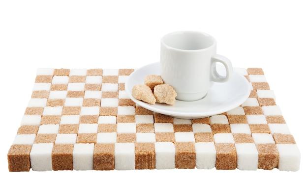 Tasse à café vide sur une soucoupe avec trois morceaux de cassonade sur un support de sucre blanc et brun.