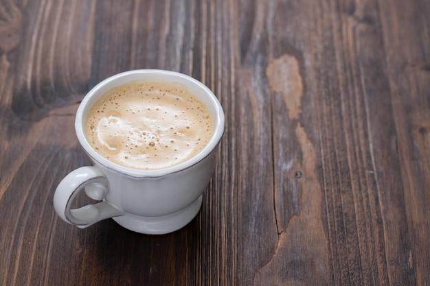 Une tasse de café sur une vieille surface en bois
