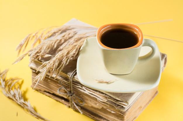 Une tasse de café sur de vieux livres et des épis de maïs secs dans une lumière jaune et crue. bien-être, harmonie, inclusion