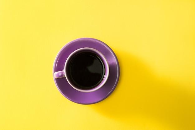 Tasse de café violet sur fond jaune