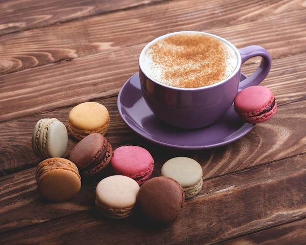 Tasse de café violet et macarons sur la table en bois