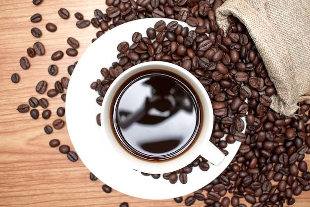 Tasse à café vue de dessus avec sac de café sur la table en bois.
