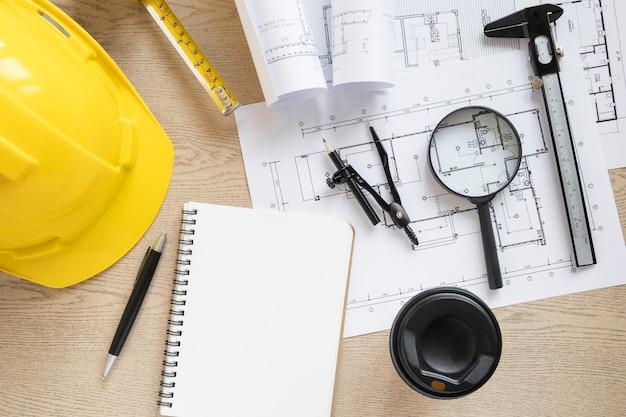 Tasse et cahier près des matériaux de construction