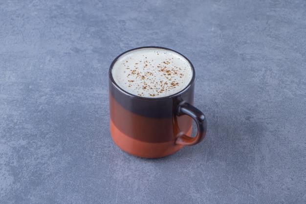 Une tasse de cappuccino au lait , sur fond bleu.