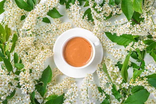 Une tasse à cappuccino blanc parmi les branches fleuries. fond floral, vue de dessus.