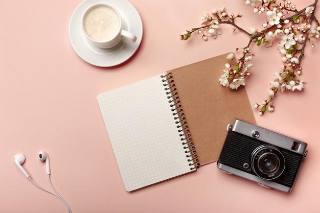 Une tasse à cappuccino blanche avec des fleurs de sakura, un carnet de notes, un appareil photo, des écouteurs