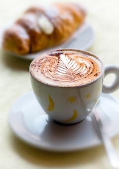 Tasse de cappuccino chaud avec une brioche