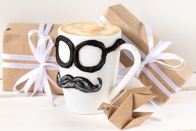 Une tasse de cappuccino chaud et des cadeaux pour la fête des pères.