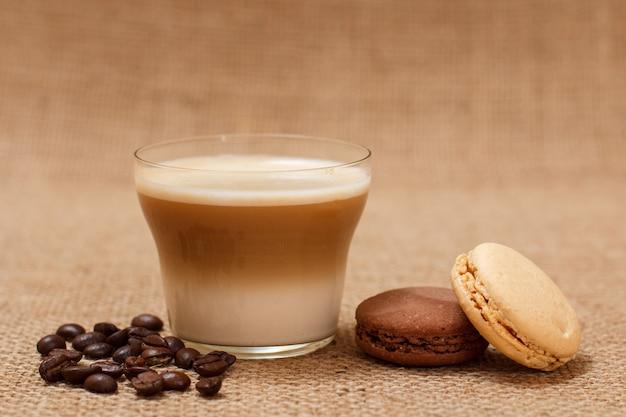 Tasse de cappuccino, grains de café et macarons sur fond de sac.