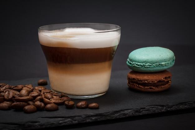 Tasse de cappuccino, grains de café et macarons sur planche de pierre noire et fond sombre.