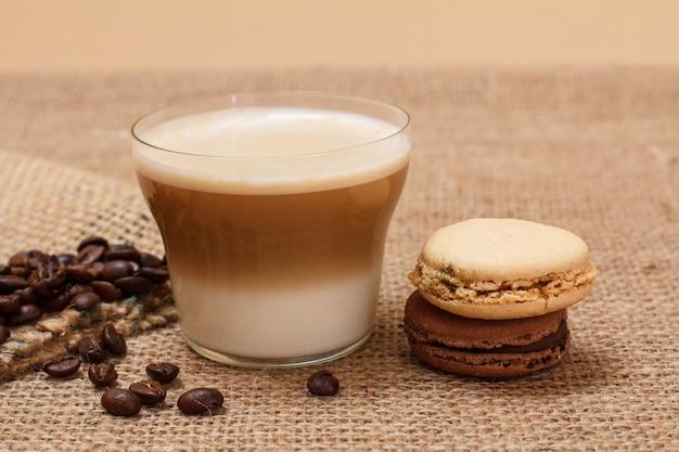 Tasse de cappuccino, grains de café avec sac en toile et macarons sur fond de sac.
