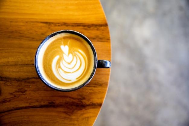 Tasse de cappuccino avec latte art sur fond en bois. belle mousse, bureau en bois et mur de briques.