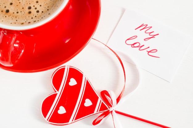 Une tasse de cappuccino rouge avec un coeur en bois et des notes mon amour.