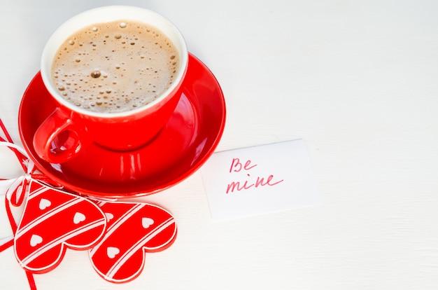Une tasse de cappuccino rouge avec un coeur en bois et des notes soyez à moi.