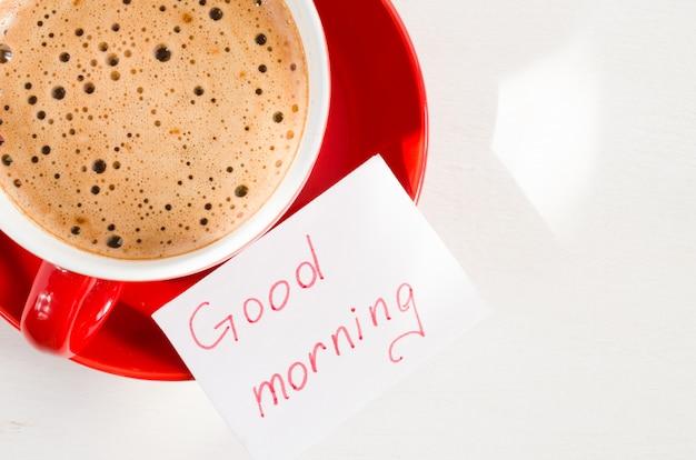 Une tasse de cappuccino rouge et des notes bonjour sur un tableau rustique clair.