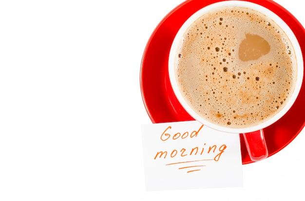 Une tasse de cappuccino rouge et des notes bonjour.