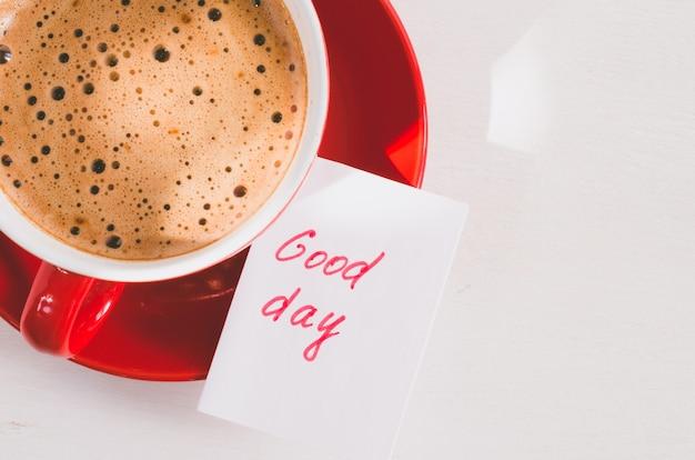 Une tasse de cappuccino rouge et de notes good day on light rustic table