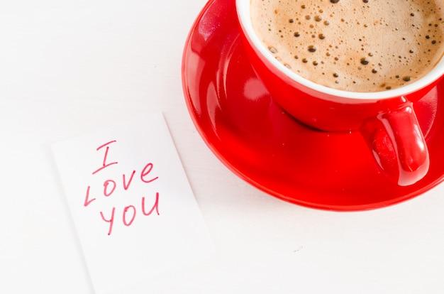 Une tasse de cappuccino rouge et des notes je t'aime sur une table rustique claire.