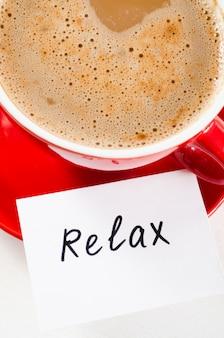 Une tasse de cappuccino rouge et des notes se détendre sur une table rustique claire.