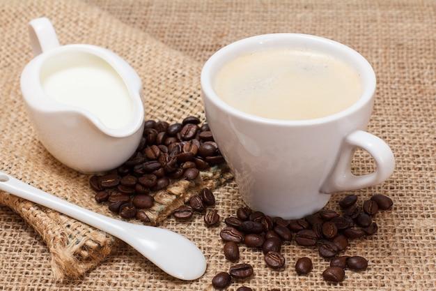 Tasse de cappuccino, saucière crème, cuillère, grains de café et sac de toile sur un sac.