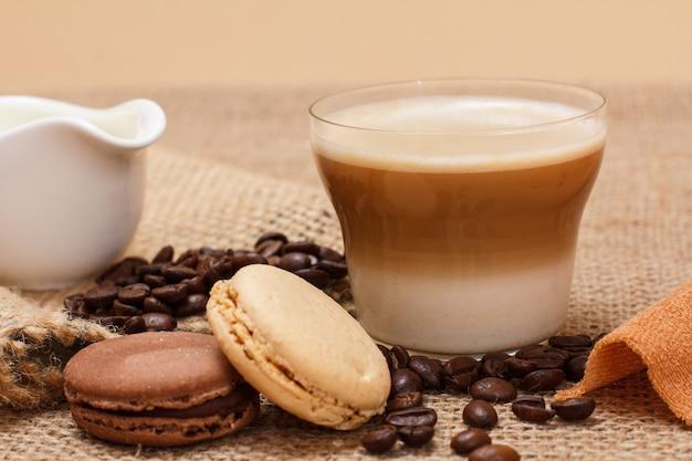 Tasse de cappuccino, saucière à la crème, grains de café et macarons sur fond de sac.