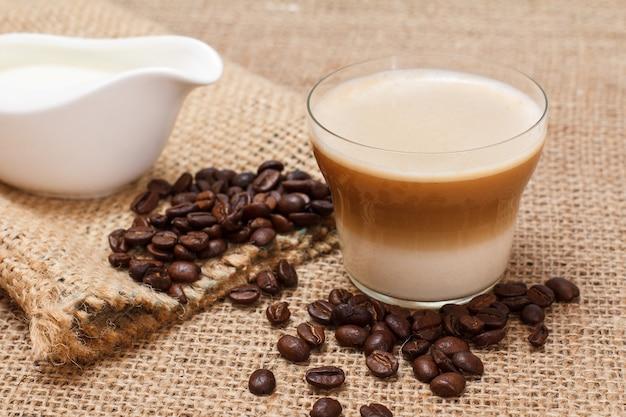 Tasse de cappuccino, saucière crème, grains de café et sac de toile sur un sac.