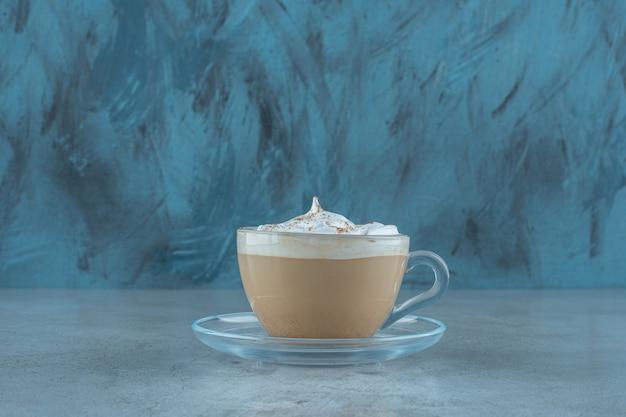 Une tasse de cappuccino sur une soucoupe , sur la table bleue.
