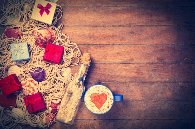 Tasse de cappuccino avec symbole en forme de coeur, cadeau et filet avec coquilles et bouteille sur bois