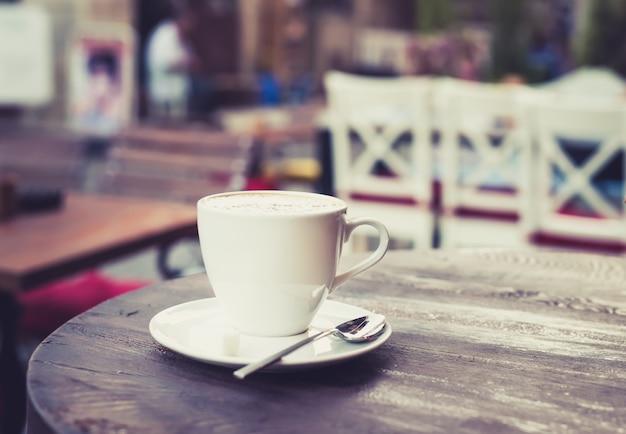 Tasse de cappuccino sur une vieille table en bois sombre dans un café de rue