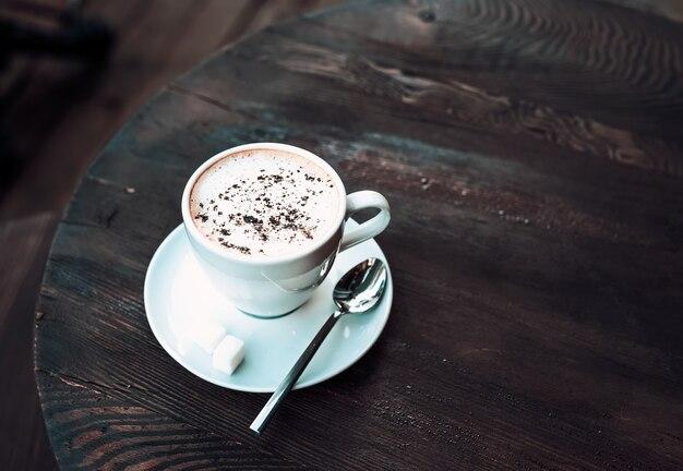 Tasse de cappuccino sur une vieille table en bois sombre