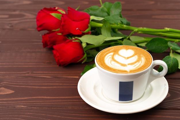 Tasse de cappucino avec art et bouquet de roses sur table en bois se bouchent