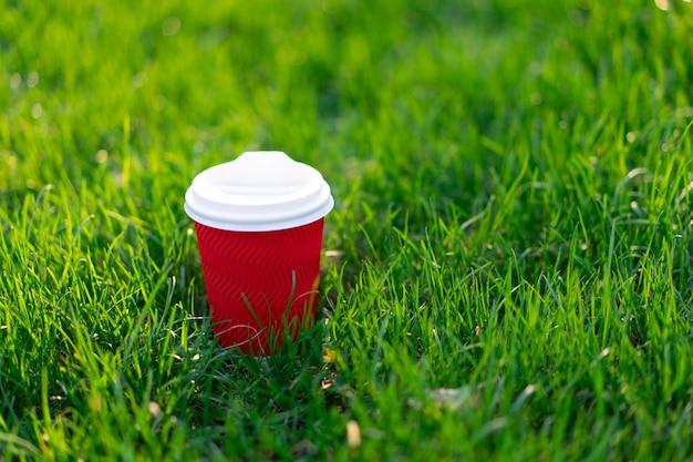 Une tasse en carton jetable rouge avec du thé chaud se dresse dans l'herbe verte fraîche.