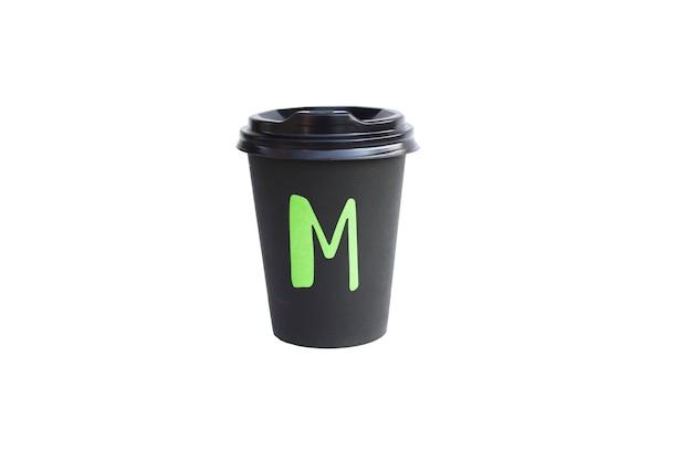Tasse en carton noir jetable isolée sur une surface blanche, tasse eco pour café et thé. concept d'idée d'écologie.