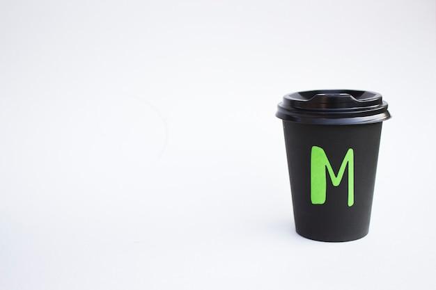 Tasse en carton noir jetable isolée sur une surface blanche, tasse eco pour café et thé. espace de copie de concept idée écologie