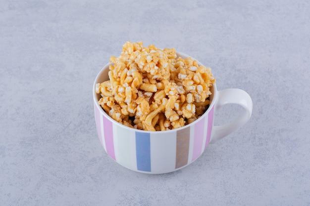 Tasse en céramique de bonbons durs avec noix sur pierre.
