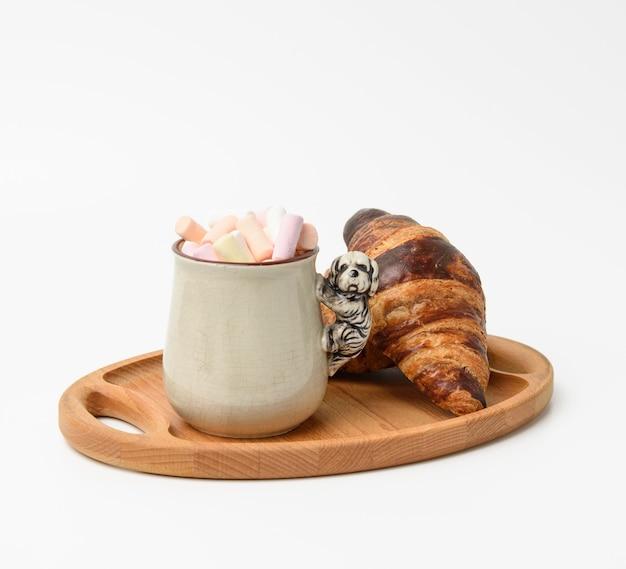 Tasse en céramique avec cacao et guimauves, croissant cuit au four sur une assiette en bois, nourriture sur fond blanc