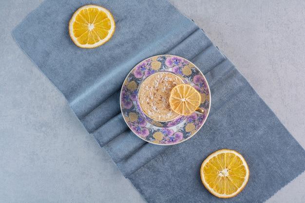 Une tasse en céramique de café chaud mousseux placé sur un tissu bleu.
