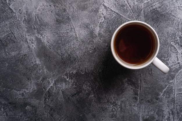 Une tasse en céramique avec du thé noir chaud, boire dans une tasse de thé blanc sur une table en pierre sombre texturée, vue de dessus copie espace