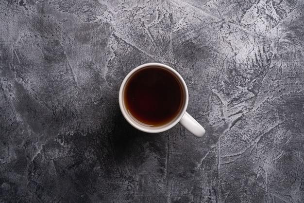 Une tasse en céramique avec du thé noir chaud