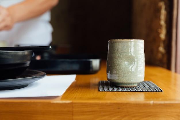 Tasse en céramique japonaise de thé vert sur une table en bois.