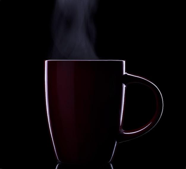 Tasse en céramique rouge de boisson chaude à la vapeur isolée sur fond noir. silhouette.