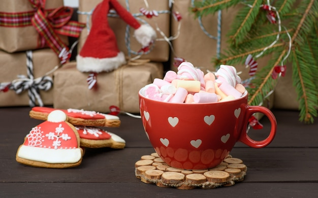 Tasse en céramique rouge avec cacao et guimauves, derrière un coffret cadeau et un jouet de noël