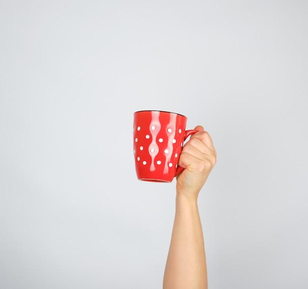 Tasse en céramique rouge dans une main féminine