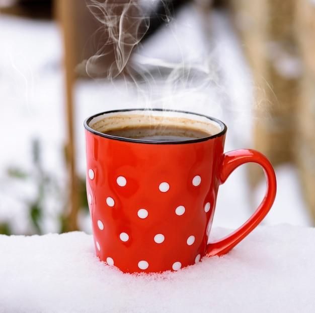Tasse en céramique rouge à pois blancs avec café noir chaud