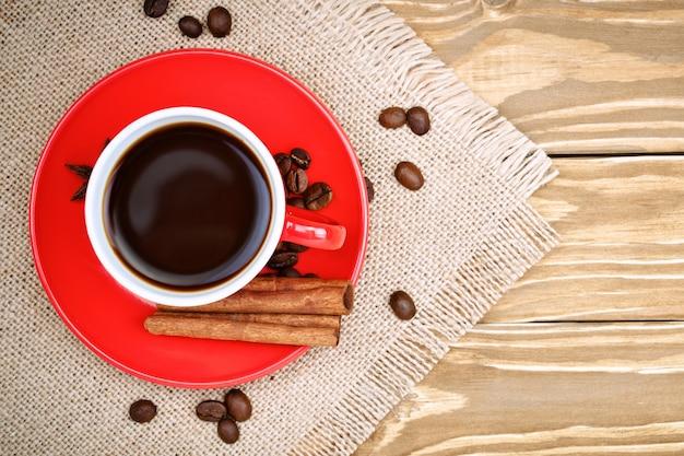 Tasse en céramique rouge avec support à café sur des planches en bois et toile de jute avec des grains de café dispersés.