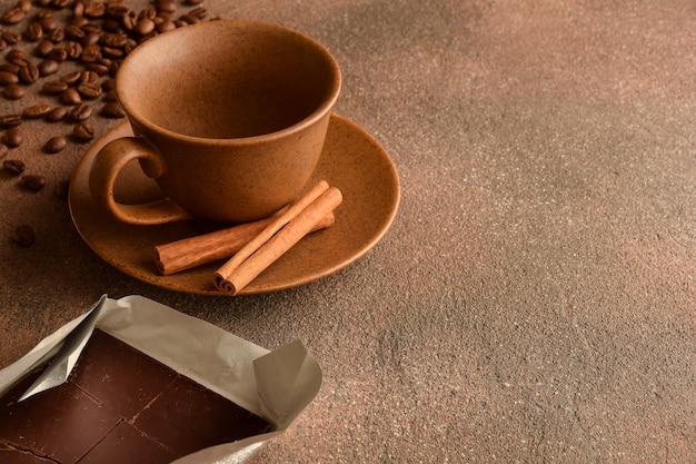 Tasse en céramique vide avec soucoupe, cannelle, grains de café dispersés et chocolat sur une surface en pierre