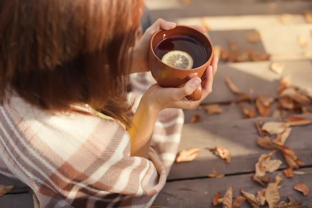 Tasse chaude de café chaud se réchauffant entre les mains d'une femme