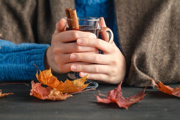 Tasse chaude de vin chaud chaud réchauffé entre les mains d'une fille