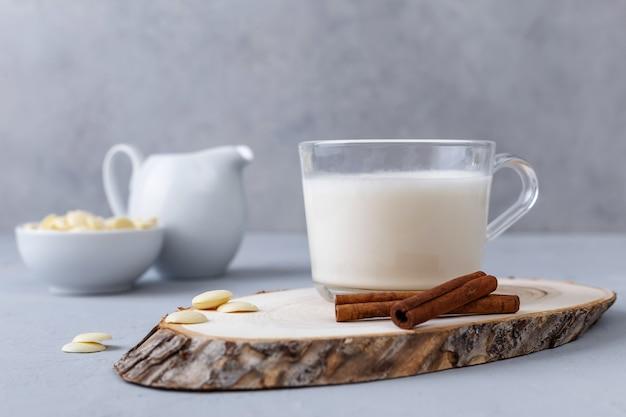 Une tasse de chocolat chaud blanc et des bâtons de cannelle sur un support en bois sur une surface grise. boissons céto.