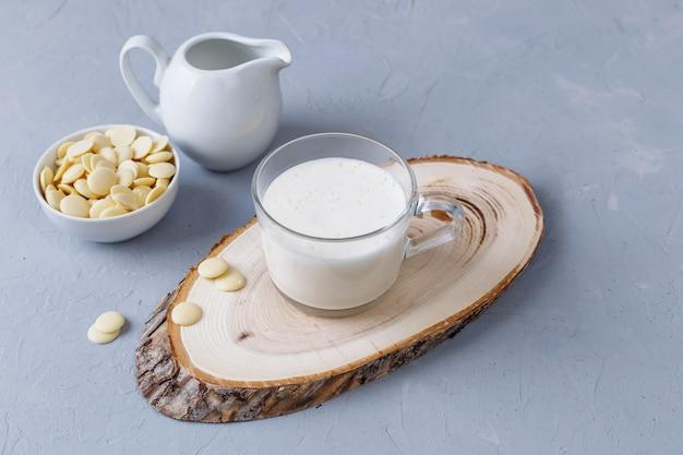 Une tasse de chocolat chaud blanc sur un support en bois sur une surface grise. boissons céto. copiez l'espace.